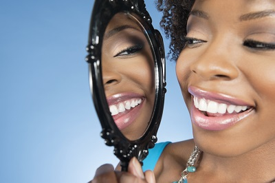 African American woman smiles in mirror after receiving restorative dental services from Boones Landing Dental Center.