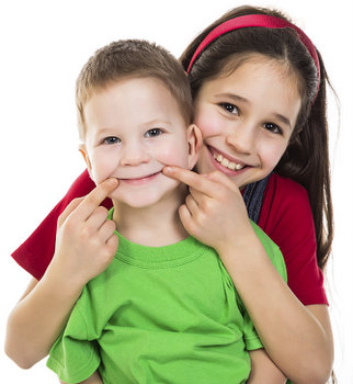 Little boy and girl hugging and smiling about no cavities at the dentist!