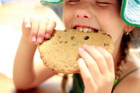A little girl eating a large cookie.